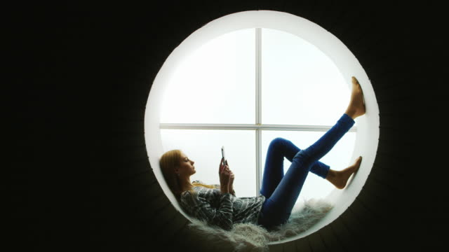 profile of a young woman who is sitting at the round window. use tablet - тур соревнований стоковые видео и кадры b-roll