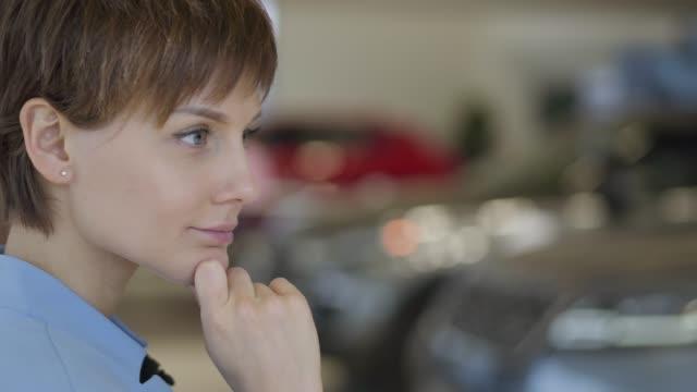 モーターで車を買うことを考えるショートヘアカットの若い女性のプロフィール - 展示会点の映像素材/bロール