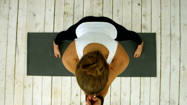 Profile of beautiful young woman doing twin in yoga class video