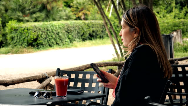 Profile of blond business Woman Talking On Smartphone with speakerphone- outdoor video