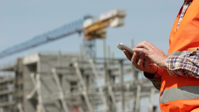 Profile of construction worker using his smartphone video