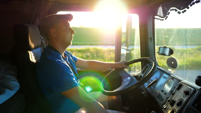 Profile of lorry driver riding through countryside at sunset time. Man in hat controlling his truck and enjoying journey. Beautiful landscape with bright sunlight at background. Slow motion Close up Profile of lorry driver riding through countryside at sunset time. Man in hat controlling his truck and enjoying journey. Beautiful landscape with bright sunlight at background. Slow motion Close up car transporter stock videos & royalty-free footage