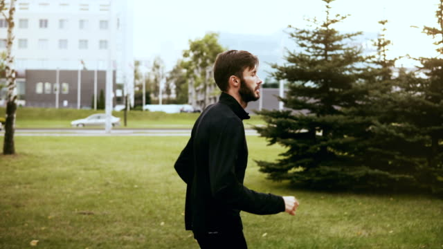 4K Profile of sportsman run fast near city street. Real time. Side view. Handsome bearded European man jogging exercise