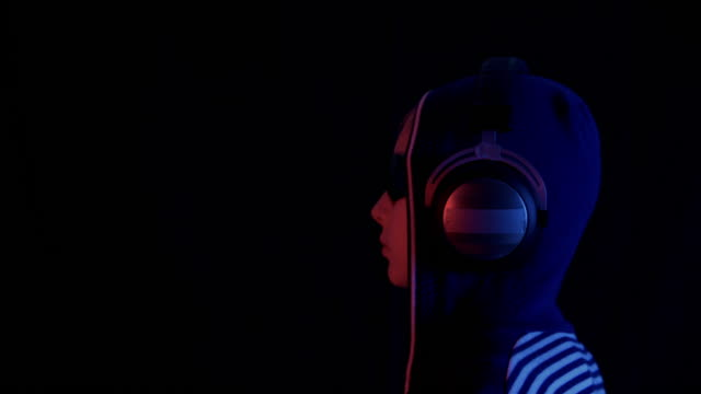 Profile of teenager in hoodie, sunglasses and headphones in darkness