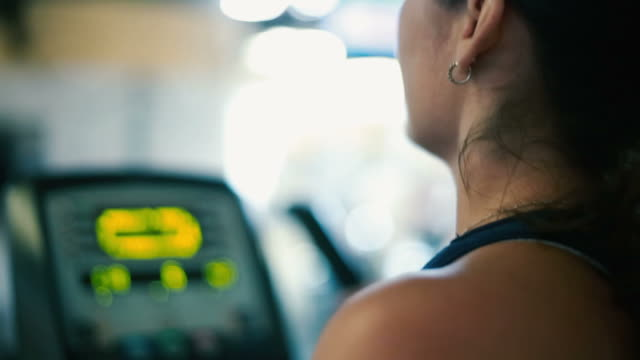 Profile of woman working out on elliptical machine at gym video