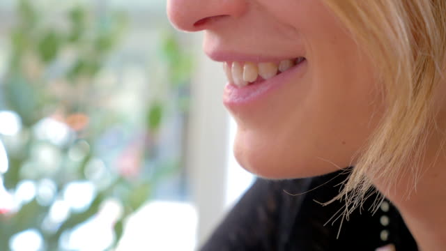 profile of young blonde woman while eating ice cream - łyżka sztućce filmów i materiałów b-roll
