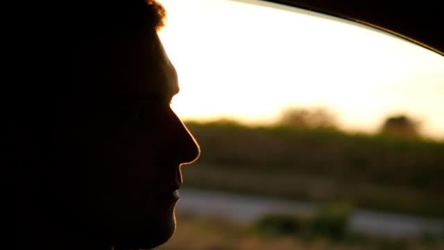 Voir le profil:: jeune bel homme conduit une voiture au coucher du soleil. Guy au volant de la voiture sous un ciel coucher de soleil à l'extérieur. Garçon à l'intérieur de sa voiture. Heure d'été. Gros plan - Vidéo