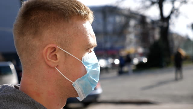 Profile of young man with medical face mask walks at city street. Guy wearing protective mask from virus outdoor in the people crowdy. Concept of health and safety life from coronavirus and pandemic
