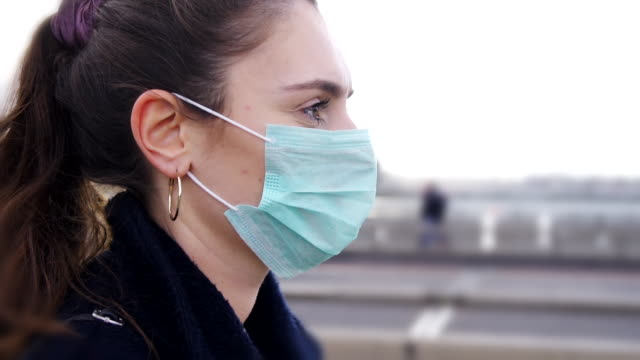 vídeos de stock e filmes b-roll de profile of young woman wearing face mask while walking in the streets of london - reino unido