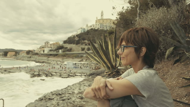 Retrato de Perfil de mujer adulta con agitando el océano en el fondo - vídeo