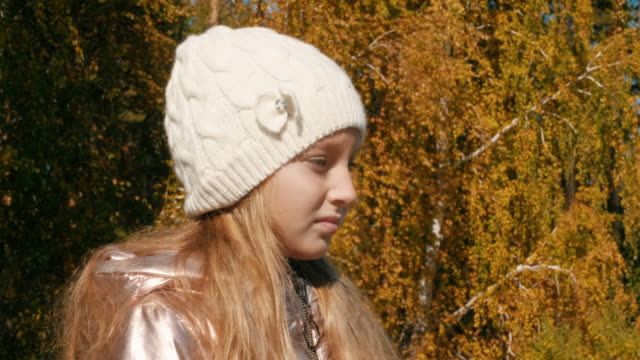 Profile portrait of sad girl looking sideway in autumn park Profile portrait of sad young girl looking sideway in autumn park with empty space for text. Preteen serious child in white hat, side view sideways glance stock videos & royalty-free footage