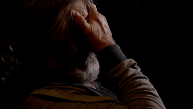Profile portrait of tired senior man rubs his eyes at dark room video