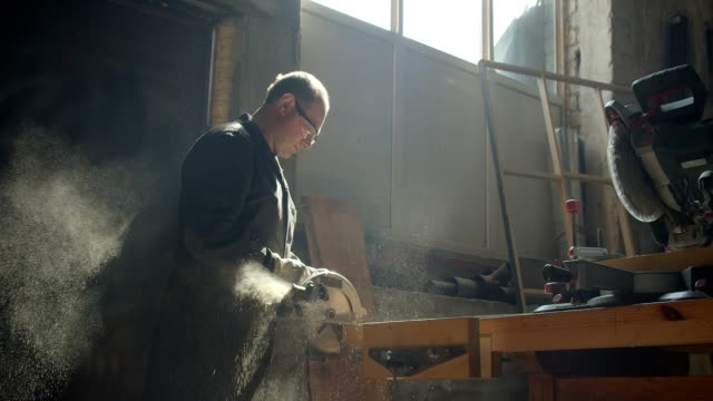 Profile shot of senior male master working at manufacture polishing the wooden board. Profile shot of senior male master working at manufacture polishing the wooden board power tool stock videos & royalty-free footage