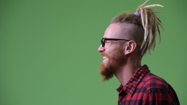 profilansicht des glücklichen bärtigen hipster-mannes mit dreadlocks lachend - mann bart freisteller stock-videos und b-roll-filmmaterial