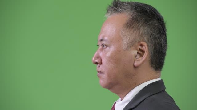 profilvyn mogen japansk affärsman mot grön bakgrund - kostym sida bildbanksvideor och videomaterial från bakom kulisserna
