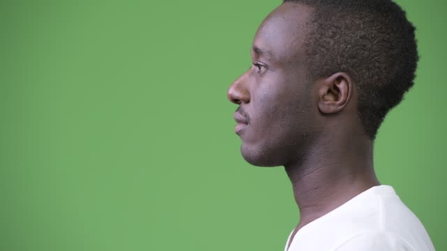 Profile view of young African man against green background