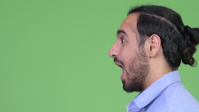 Profile view of young bearded Indian businessman screaming and looking surprised Studio shot of young handsome bearded Indian businessman against chroma key with green background mouth open stock videos & royalty-free footage
