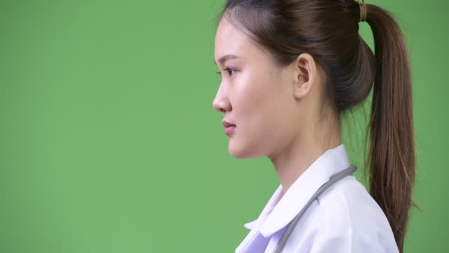 profile view of young happy beautiful asian woman doctor smiling - юго восток стоковые видео и кадры b-roll
