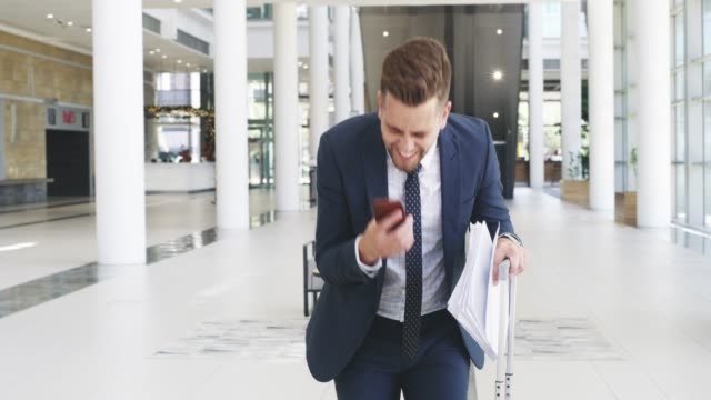 Profit keeps a business engine running 4k video footage of a young businessman throwing his paperwork in the air after receiving good news on his smartphone incentive stock videos & royalty-free footage