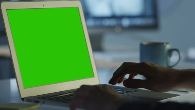 Programmeur travaille au bureau d'ordinateur portable avec écran vert pour maquette - Vidéo
