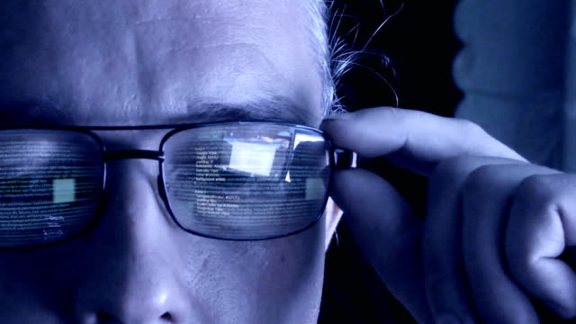 Programmer or hacker in glasses looking on monitor - software code reflecting in the glass.