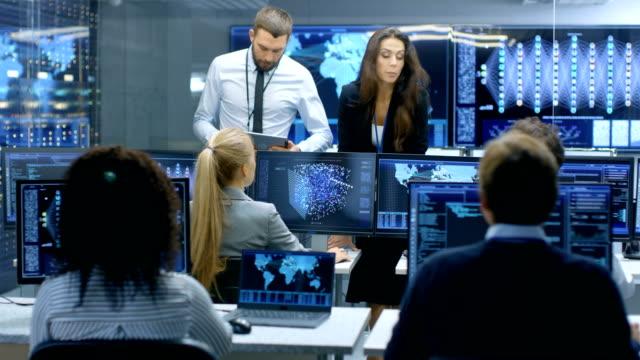 Chef de projet et chef du département détiennent Briefing pour une équipe d'ingénieurs et de programmeurs qui sont bâtiment Machine Learning System. Affichages montrent l'utilisation de modèle de réseau neuronal. - Vidéo