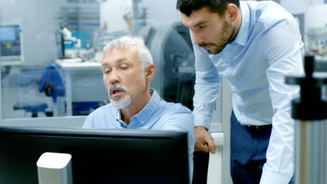 Chef de projet et Senior ingénieur projet ont Conversation connexes tout en travaillant sur ordinateur personnel. Sortis de l'usine de fabrication électronique de bureau fenêtre est Visible. - Vidéo