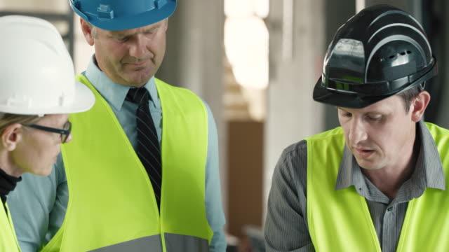 Chef de projet, discuter des détails du plan avec les architectes sur le site de construction - Vidéo