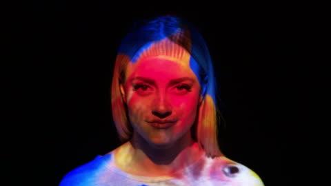vídeos de stock e filmes b-roll de projection of a goldfish on a woman's face - imagem a cores