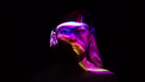 vídeos de stock e filmes b-roll de projection of multicolored smoke on a woman's face - imagem a cores