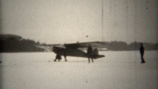 1939: Propeller snowski biplanes taxi on frozen lake.