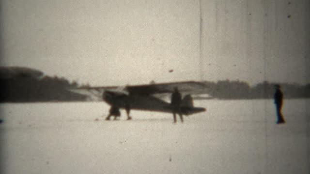 1939: プロペラ snowski 複葉機は、凍った湖でタクシーします。 - 古風点の映像素材/bロール