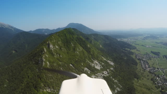 LD Propellers on the plane slowly turning while flying along a forest covered mountain ridge in sunshine Wide locked down shot of propellers on the light plane slowly turning while it flies along a forest covered mountain ridge on a sunny day. Shot in Slovenia. propeller stock videos & royalty-free footage