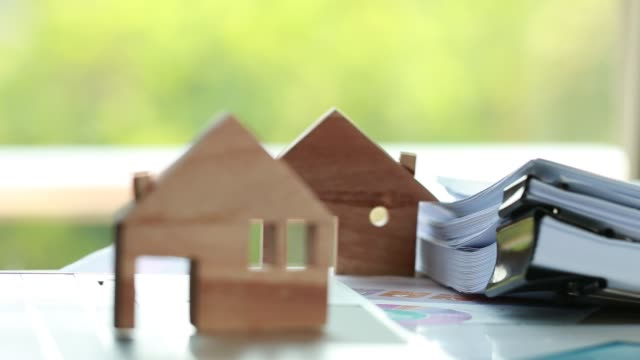 Property real estate mortgage loan or investment concept: Wooden home model on computer with chart report documents and wealth management for loan agreement to buy, that important factor of people's