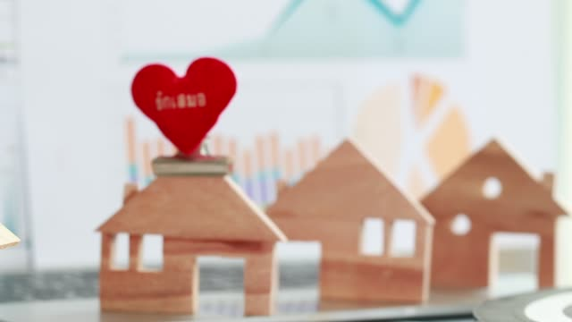 Property real estate mortgage loan or investment concept: Wooden home model with heart shape on computer with chart report documents,wealth management for agency online contact agreement of people's