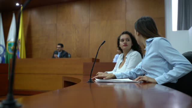 Prosecutor and client at the courtroom talking during the trial video