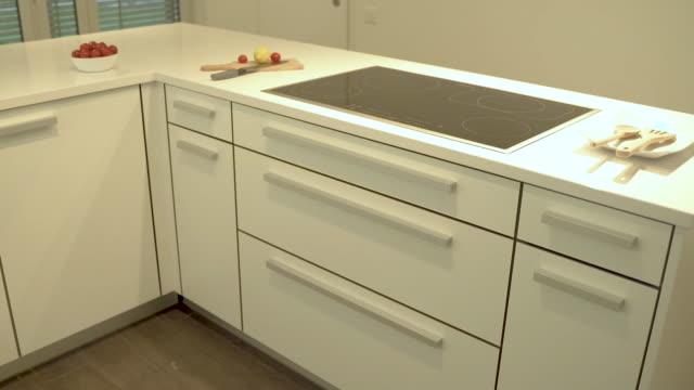 Prospective view of modern kitchen design in white kitchen cabinets and quartz countertop