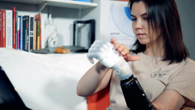 Prosthetic hand is being regulated by a lady and used for typing Prosthetic hand is being regulated by a lady and used for typing. 4K robot stock videos & royalty-free footage