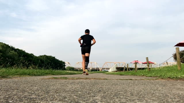 prosthetic legged japanese man running in a park - solo un uomo maturo video stock e b–roll