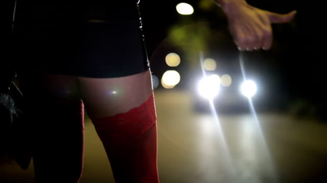 Prostitute hitchhiking One woman, young prostitute in mini skirt, standing on the street hitchhiking at night. human trafficking stock videos & royalty-free footage