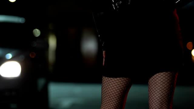 vídeos y material grabado en eventos de stock de prostituta en mallas a cuadros esperando a los clientes en la carretera, molesto por pasar el coche - human trafficking