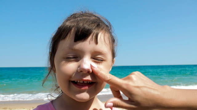 protecting kids face from sun. - sun cream stock videos & royalty-free footage