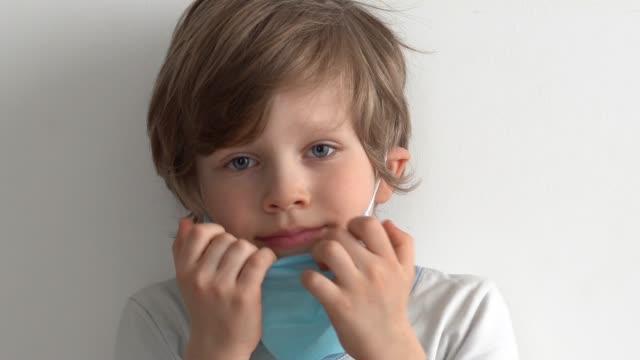 skydd mot coronavirus. lilla pojke sätter en mask på hennes ansikte. - face mask bildbanksvideor och videomaterial från bakom kulisserna