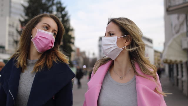 protection.two young women with pollution masks  walking down the street - amicizia tra donne video stock e b–roll