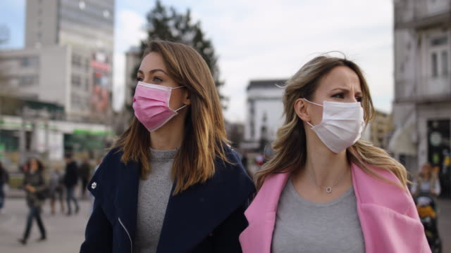 Protection.Two young women with pollution masks  walking down the street video