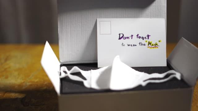 vidéos et rushes de masque protecteur de visage dans la boîte-cadeau avec la carte postale manuscrite sur la table - carte postale
