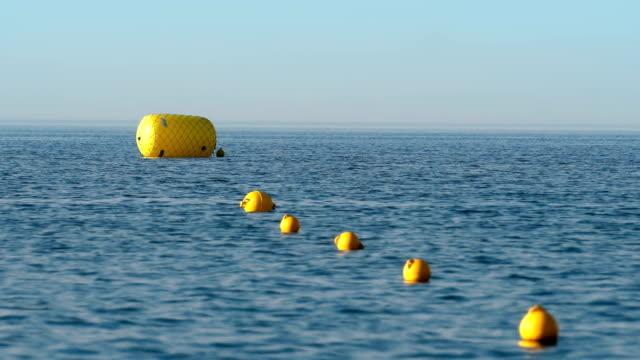 vídeos de stock, filmes e b-roll de bóia de proteção dos flutuadores na corda na praia na água, foco seletivo - boia salva vidas