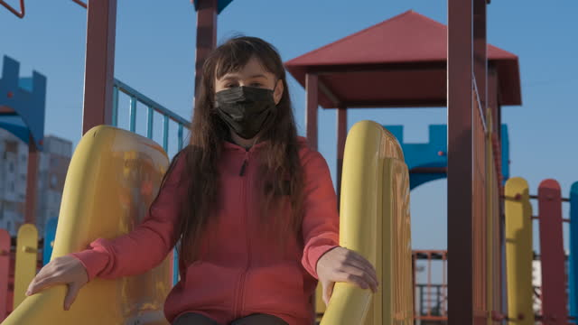 Protective play mood. Protective play mood. A child protect herself with a protective mask on a slide in the day light. russian ethnicity stock videos & royalty-free footage