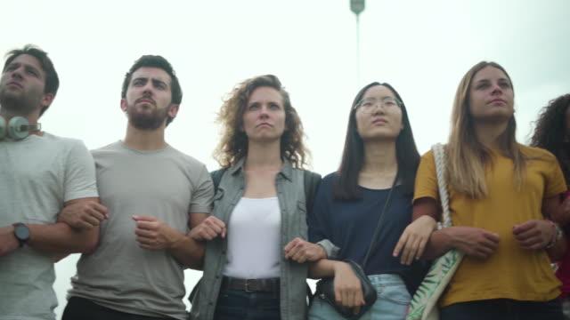 protestors standing together outdoors - fianco a fianco video stock e b–roll