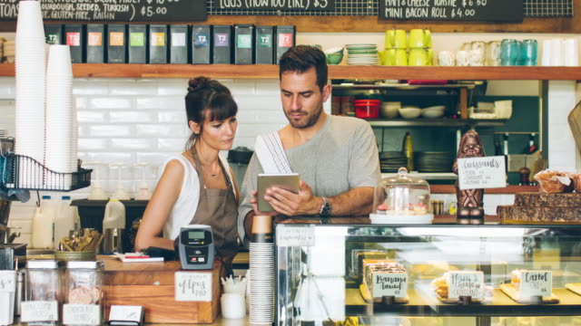 Proud about their new business Proud coffee shop owners using a digital tablet and looking at the camera. owner stock videos & royalty-free footage